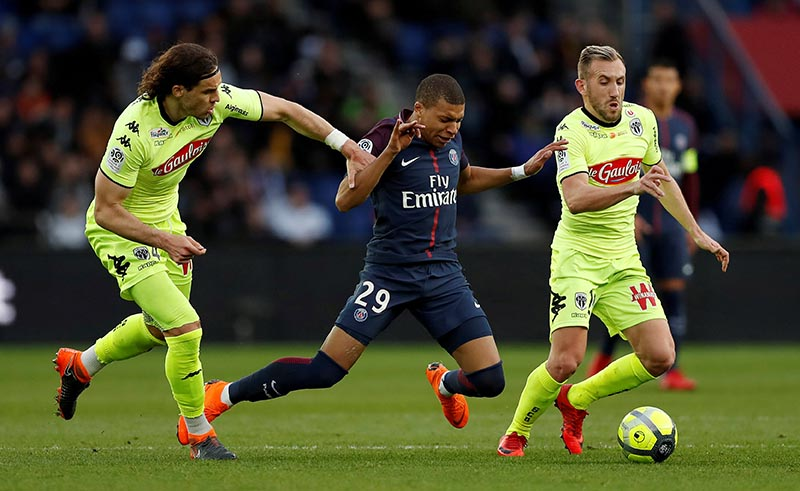 Paris Saint-Germain's Kylian Mbappe in action with Angers' Mateo Pavlovic (left) and Flavien Tait during the French Ligue 1 match between Paris St Germain and Angers, at Parc des Princes, in Paris, France, on March 14, 2018. Photo: Reuters