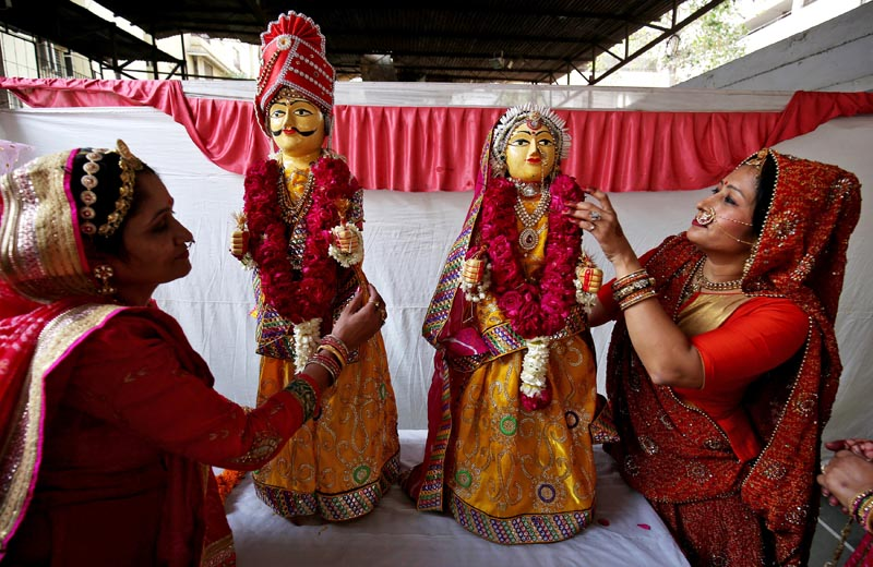 Women adorn wooden idols of a bride and a groom during Gangaur festival, during which unmarried women observe a fast for a desirable husband, while married women do so for the welfare, health and longevity of their husbands, in Ahmedabad, India, March 14, 2018. Photo: Reuters