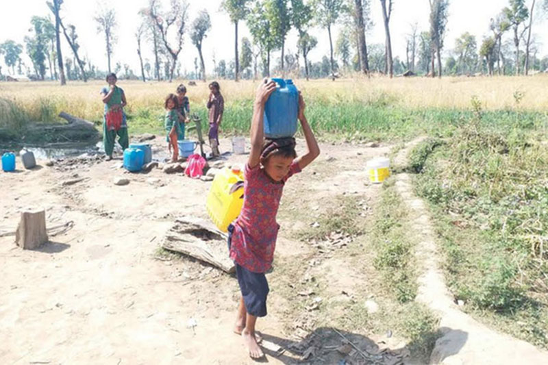 Children of Jahari village carrying water after waiting for their turns at the tube-well in the village settlement, near Sukhkhad Bazaar in Ghodaghodi Municipality-8, Kalali district, on Saturday, March 24, 2018. Photo: Tekendra Deuba