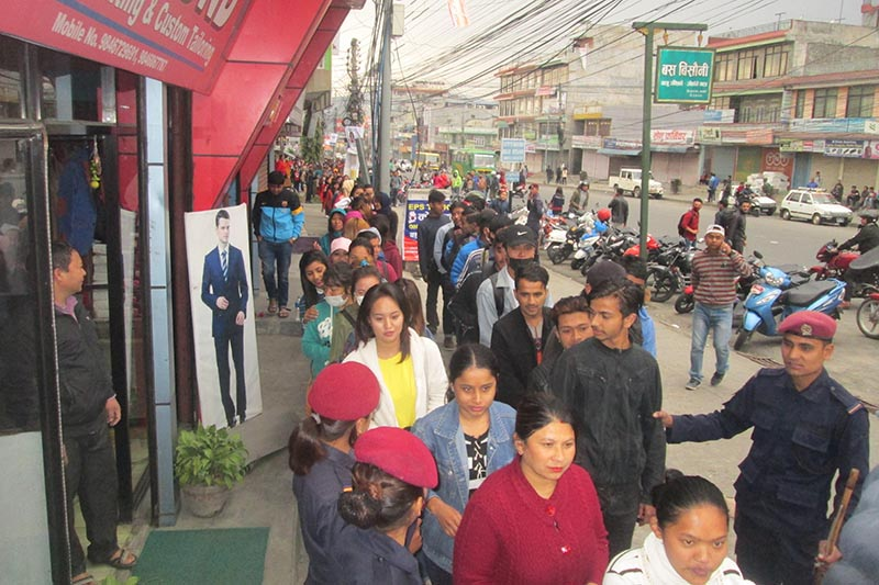 FILE PHOTO: Police personnel monitor as youths queue up along a footpath to submit applications of the Korean Language Test (KLT) under the Employment Permit System (EPS)u201a in New Roadu201a Pokhara of Kaski district on Thursdayu201a March 22, 2018. Photo: Rishi Ram Baral