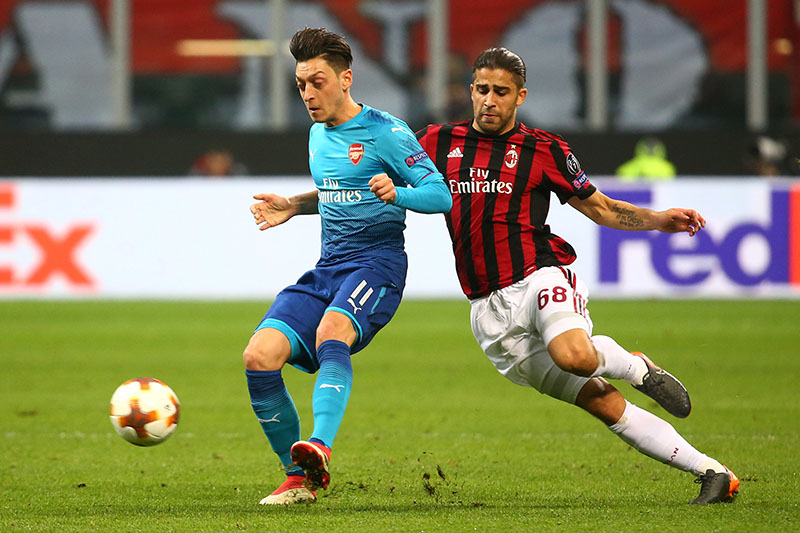 Arsenal's Mesut Ozil in action with AC Milan's Ricardo Rodriguez. Photo: Reuters