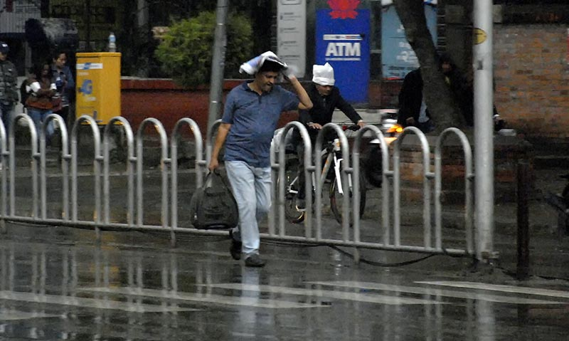A pedestrian trying to shield himself from the rain using a newspaper during a brief shower at Durbar Marg, Kathmandu, on Sunday, March 12, 2018. Photo: THT