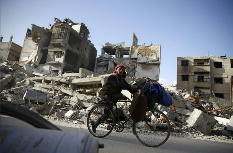 A handicapped man rides a bicycle past damaged buildings in the besieged town of Douma in eastern Ghouta in Damascus, Syria, March 1, 2018. Photo: Reuters