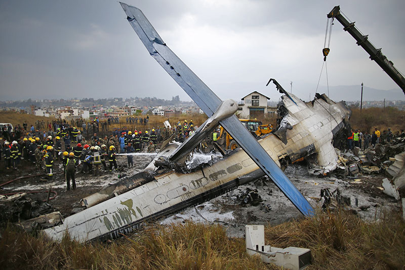 Security personnel and fire fighters trying to douse fire at the wreakage of the US-Bangla aircraft which careened off the runway before crashing onto a field at Tribhuvan International Airport in Kathmandu, on Monday, March 12, 2018. Photo: Skanda Gautam/THT