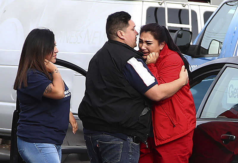 Fernando Juarez (36) of Napa (center) embraces his 22-year-old sister Vanessa Flores (right) at the Veterans Home, in Yountville, California, on Friday, March 9, 2018. Flores, who is a caregiver at the facility, exchanged texts with family while sheltering in place. Photo: AP
