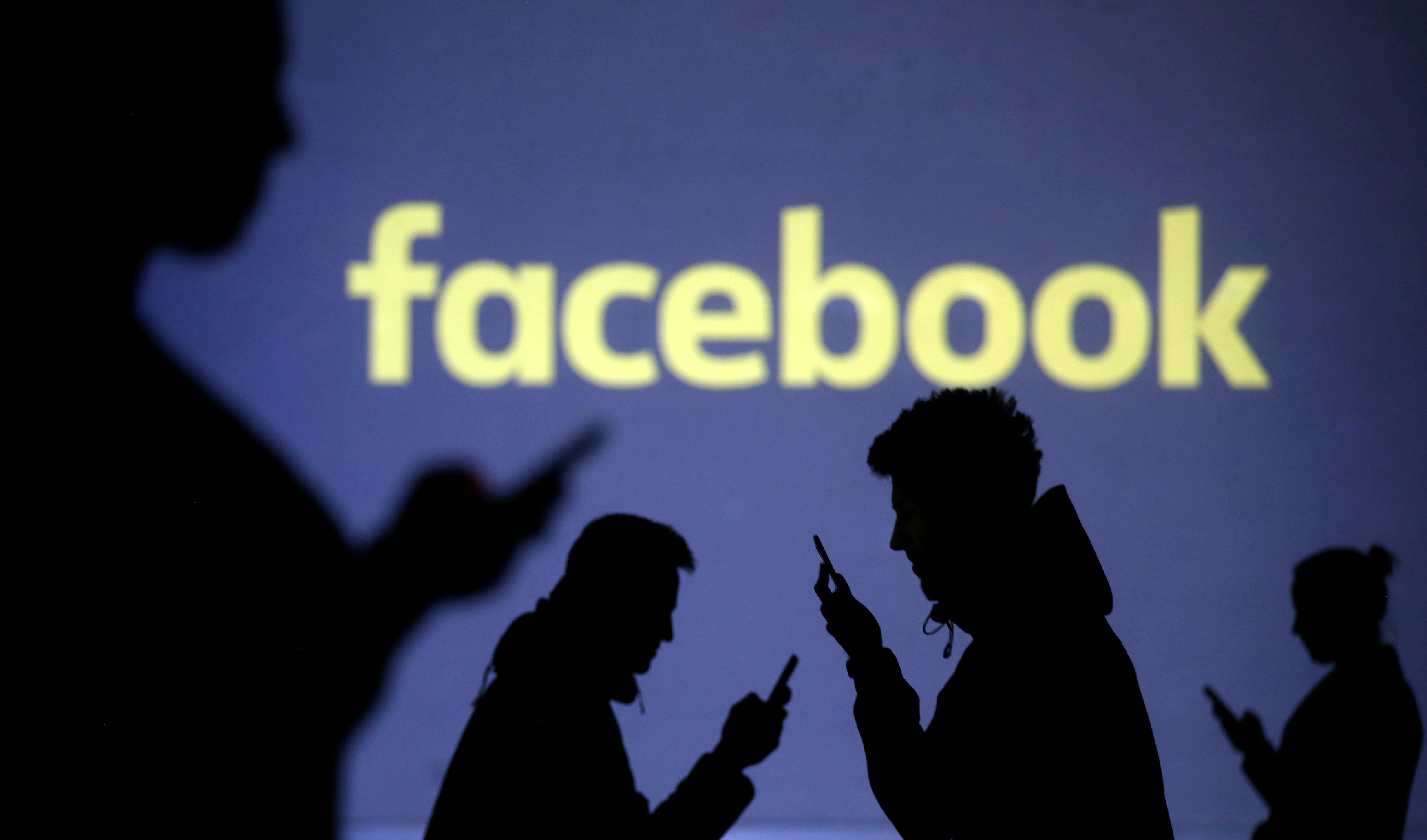 FILE PHOTO: Silhouettes of mobile users are seen next to a screen projection of Facebook logo in this picture illustration taken March 28, 2018.   Photo: REUTERS