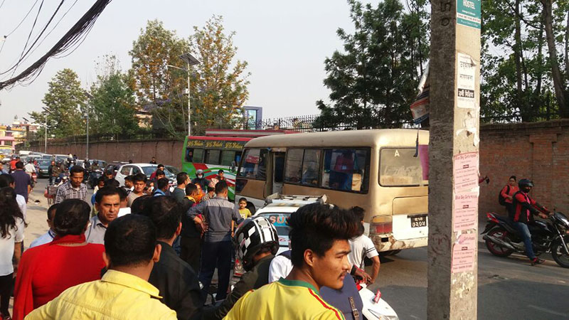 People gather around and traffic gets obstructed as a taxi rams into a Nepal Yatayat bus on the main road in Anamnagar, Kathmandu, on Tuesday, April 24, 2018. Damages were incurred on both the vehicles, however, all passengers were reported safe. Photo: Priyanka Adhikari/THT