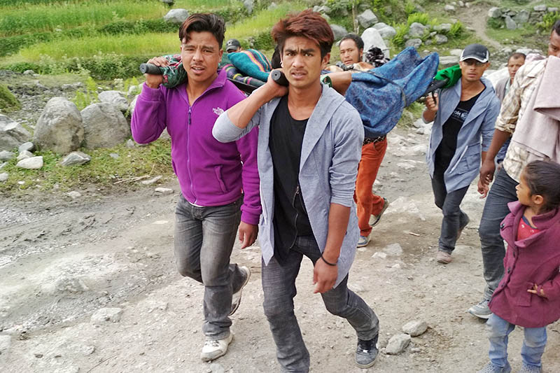 Villagers carrying patient to District Hospital after nearby Kolti Primary Health Post failed to provide treatment as health professionals remained absent, in Bajura district, on Sunday, April 22, 2018. Photo: Prakash Singh