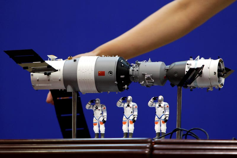 FILE- A model of the Tiangong-1 space lab module (L), the Shenzhou-9 manned spacecraft (R) and three Chinese astronauts is displayed during a news conference at Jiuquan Satellite Launch Center, in Gansu province, China June 15, 2012.  Photo: Reuters