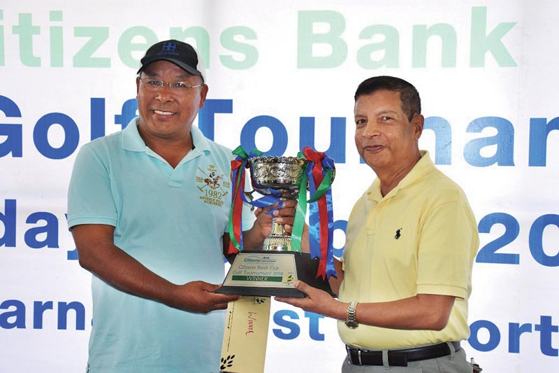 Babu Sherpa receiving the trophy from Chairman of Citizens Bank Shankar Sharma (right) after the Citizens Bank Open Golf Tournament at the Gokarna Golf Club on Saturday, April 21,2018. Photo: THT