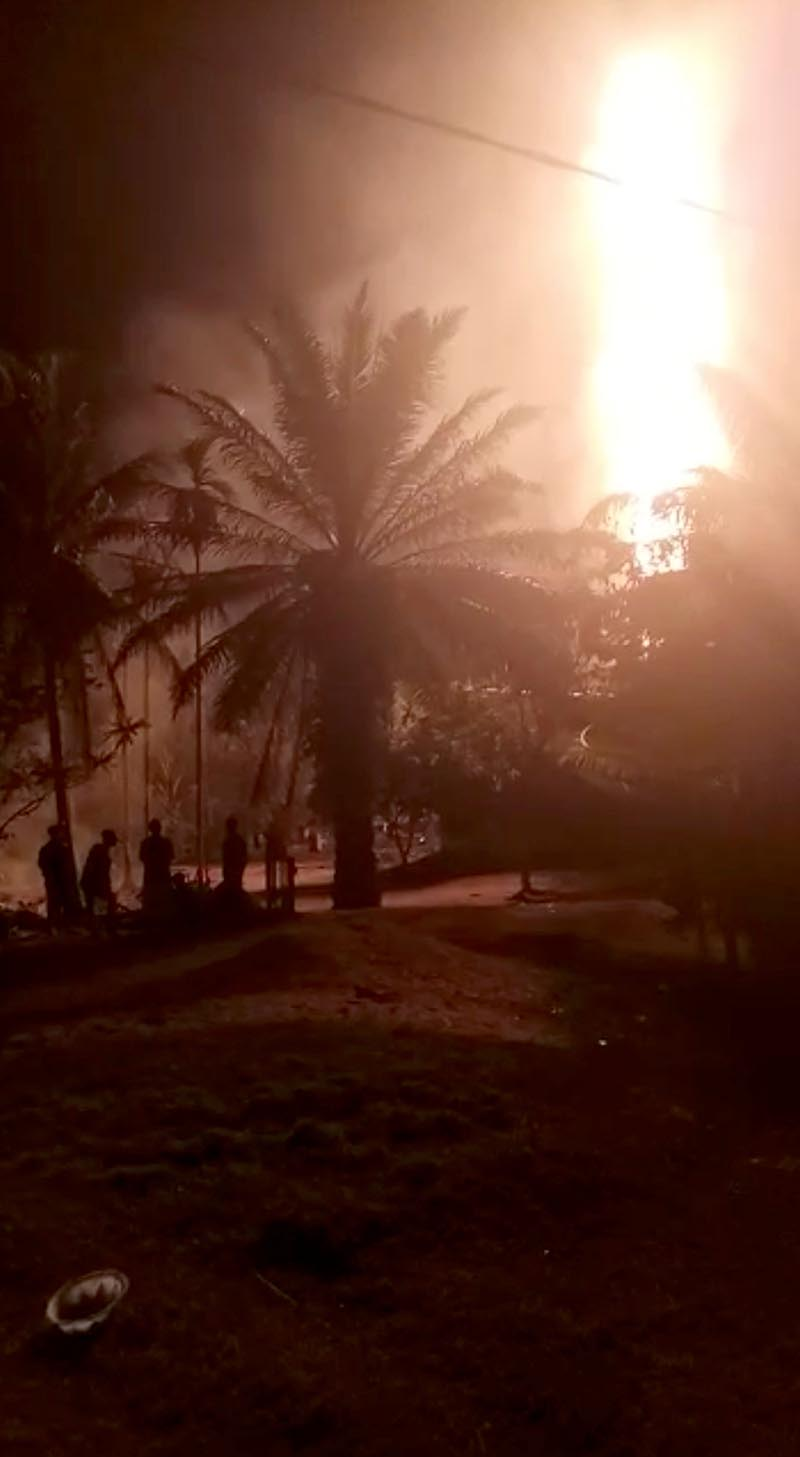People gather near the fire burning in Aceh, Indonesia, April 25, 2018 in this picture grab obtained from social media video. Photo Courtesy: ANDIKA JAYA PUTRA/via Reuters
