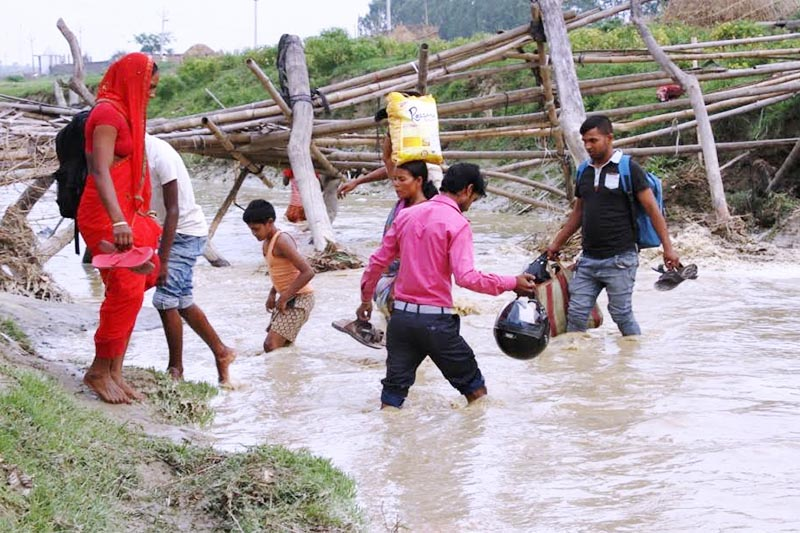 Locals crossing Khado Khola after the bamboo bridge over the stream collapsed in Tilathi Koiladi Rural Municipality,  Saptari, on Wednesday, April 18, 2018. Photo: THT