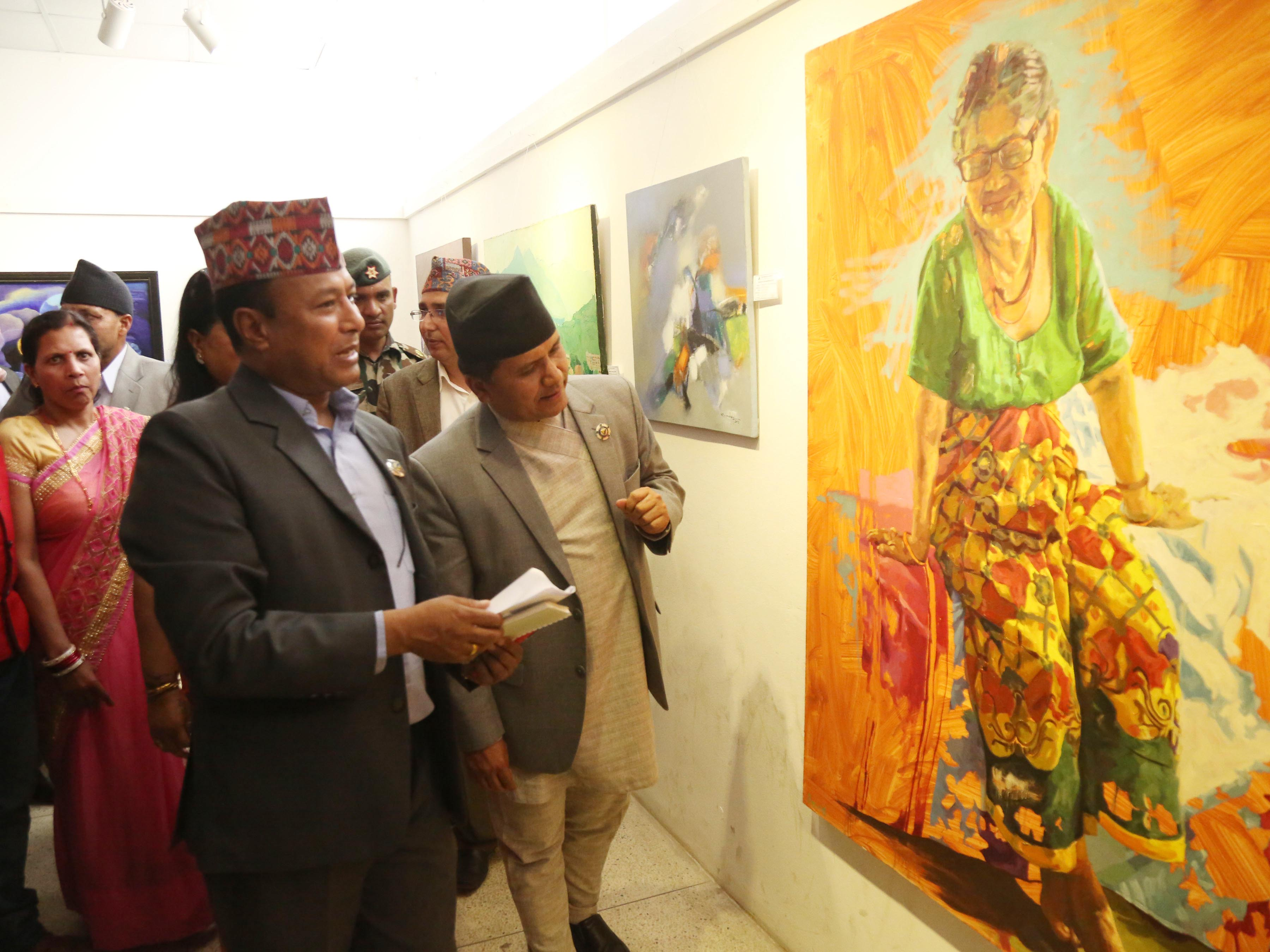 Minister for Culture, Tourism and Civil Aviation Rabindra Adhikari looking at a painting at an art nexhibition, in Kathmandu, on Wednesday, April 18, 2018. Photo: RSS