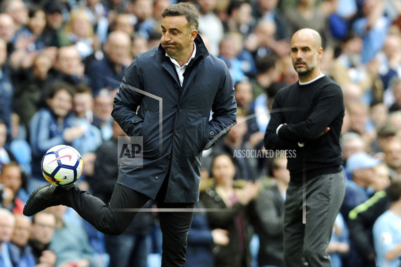 FILE - In this Sunday, April 22, 2018 file photo, Swansea manager Carlos Carvalhal, left, kicks the ball during their English Premier League soccer match against Manchester City at Etihad stadium in Manchester, England. Manager Carlos Carvalhal has left Swansea after the English Premier League club decided not to renew his contract on Friday, May 18, 2018. Swansea was relegated last Sunday after seven years in the topflight. (AP Photo/Rui Vieira, file)