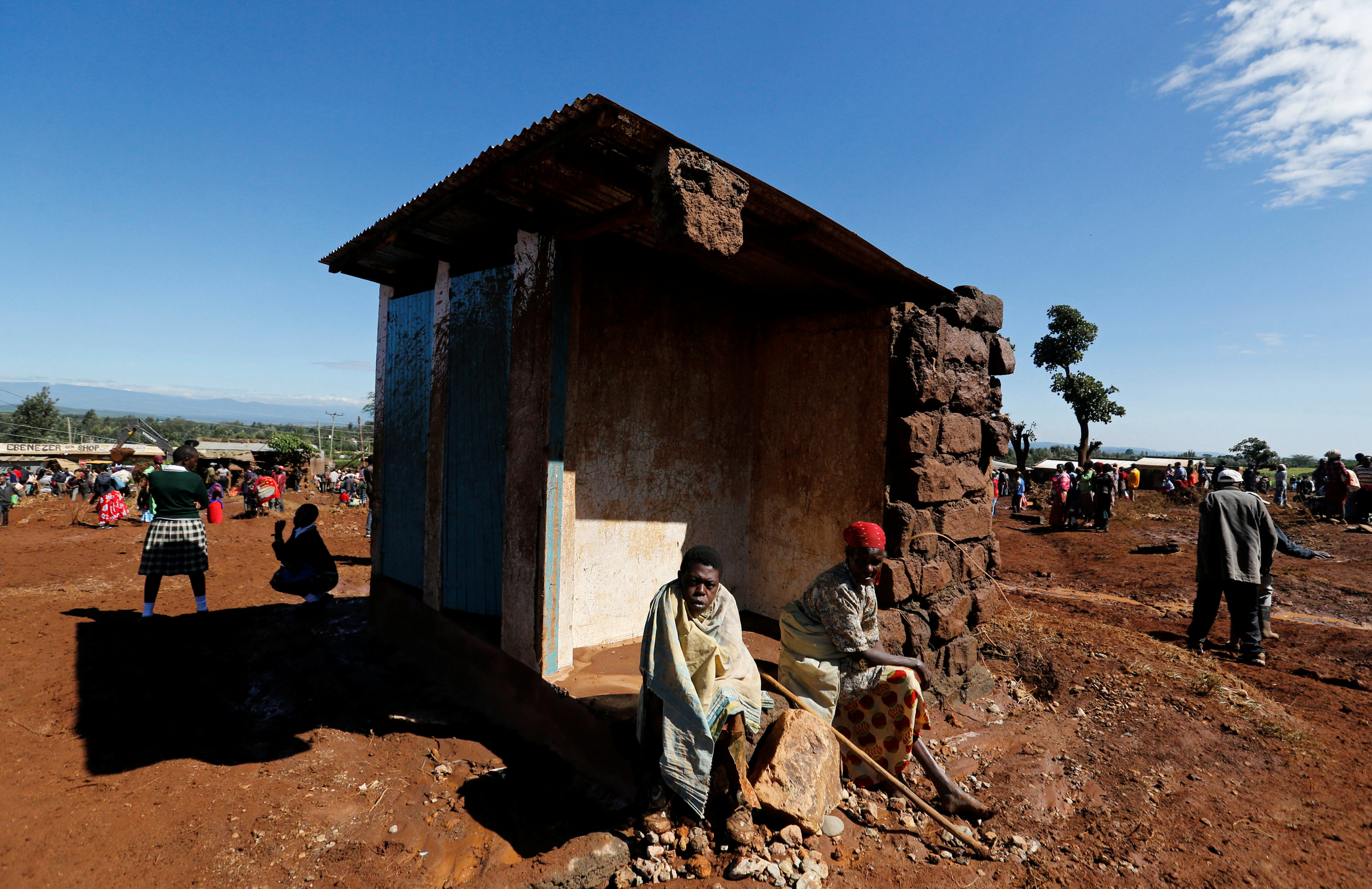 Survivors sit outside their destroyed house after a dam burst, which unleashed water at nearby homes, in Solio town near Nakuru, Kenya May 10, 2018.  Photo: REUTERS