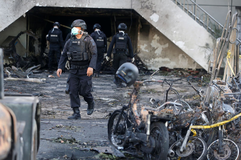 An Indonesian Special Forces Police counter-terrorism squad member walks by burned motorcycles following a blast at the Pentecost Church Central Surabaya (GPPS), in Surabaya, Indonesia May 13, 2018. REUTERS/Beawiharta