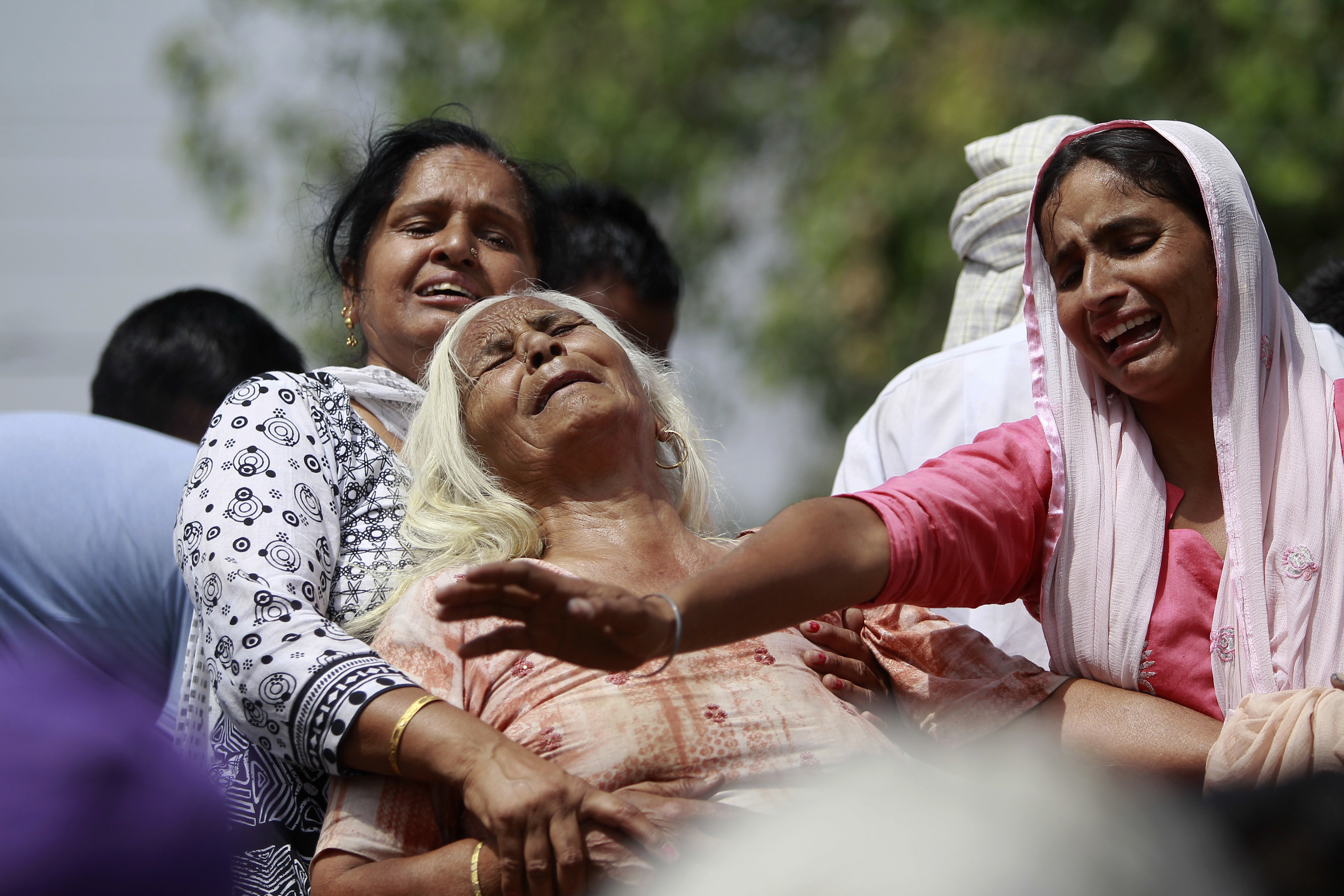 Indian women wail near the bodies of relatives, victims of cross-border firing, as they block a road during a protest against the state government in Ranbir Singh Pura, Jammu and Kashmir state, India, Friday, May 18, 2018. Eight civilians, including a husband and wife and four members of a family, were killed after Indian and Pakistani soldiers targeted border posts and villages along the highly militarised frontier in disputed Kashmir, officials said Friday. An Indian soldier was also killed in the fighting. Photo: AP