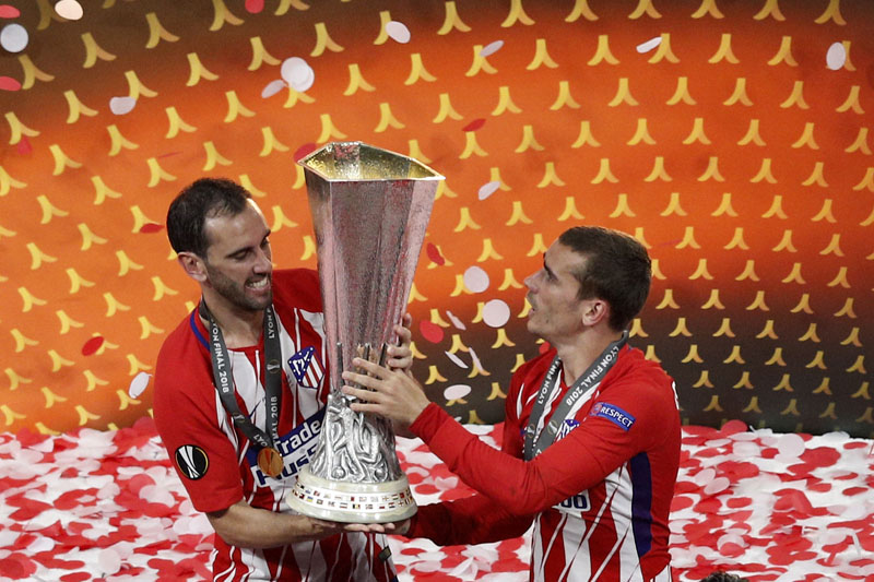Atletico's Diego Godin and Antoine Griezmann lift up the cup after the Europa League Final  match between Marseille and Atletico Madrid at the Stade de Lyon, Lyon, France, on  Wednesday, May 16, 2018. Photo: Associated Press