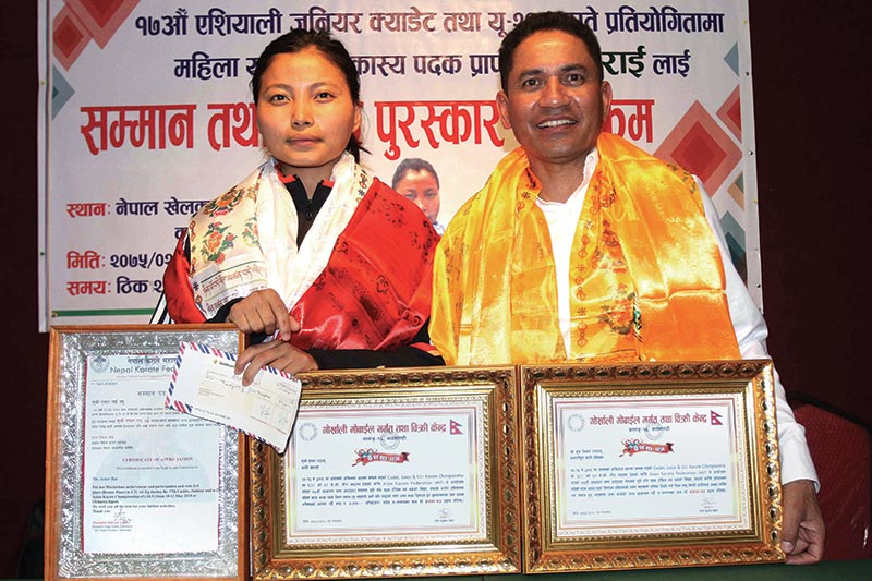 Aster Rai (left) bronze medallist of the 17th Junior Cadet and U-21 Karate Championship and coach Dhruba Bikram Malla receive letter of felicitation and cash prize orzanized by Nepal Karate Federation in Kathmandu on Tuesday.