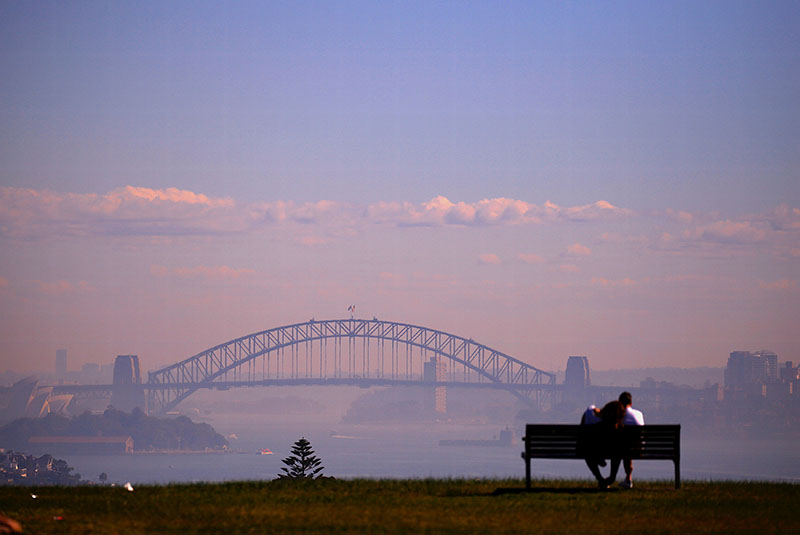 A couple sits on a seat overlooking Sydney Harbour which was covered in smoke from hazard reduction burns of bushland around the city of Sydney in Australia, on May 29, 2018. Photo: Reuters