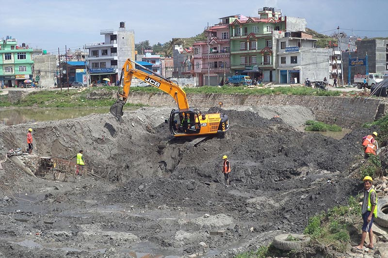 An excavator is seen digging and moving earth while construction workers are engaged in the work carried out under Bagmati embellishing project, in a 8.5-kilometre section of Bagmati River, between Gokarna Barrage and Sinamangal bridge, on Friday, May 18, 2018. Photo: RSS