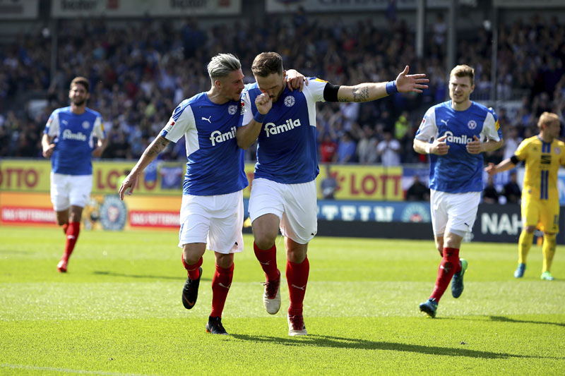 File Photo: Holstein Kiel player Rafael Czichos, center right, celebrates with Stephen Lewerenz, center left, after scoring his side's fourth goal, during the match against Eintracht Braunschweig, on Sunday May 13, 2018. Photo: Associated Press