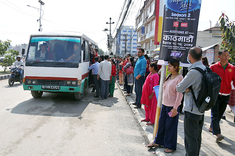 FILE: Commuters try to board a packed bus as others wait for alternative means to travel after transport entrepreneurs halted services protesting government's decision of ending transport syndicate, in Kathmandu, on Friday, May 04, 2018. Photo: RSS