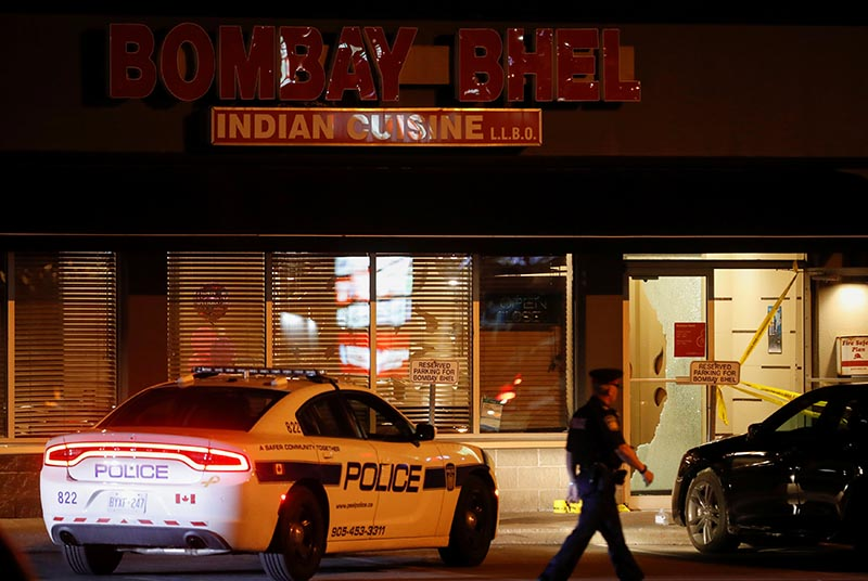 A police officer walks in front of Bombay Bhel restaurant, where two unidentified men set off a bomb late Thursday night, wounding more than a dozen people, in Mississauga, Ontario, Canada on May 25, 2018. Photo: Reuters