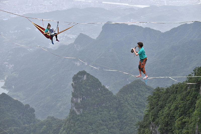 Members of performing group Houle Douce practise their instruments on tightropes ahead of a performance, at the Tianmen Mountain National Park in Zhangjiajie, Hunan province, China, on May 23, 2018. Photo: China Daily via Reuters