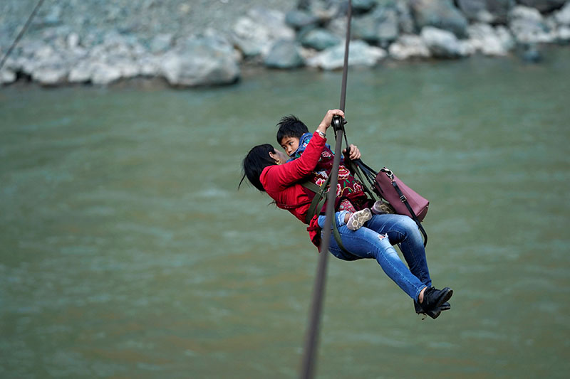 Cha Huilan, a 40-year old Lisu woman, and her daughter leave Lazimi village with a zipline across the Nu River in Nujiang Lisu Autonomous Prefecture in Yunnan province, China, on March 24, 2018.  Photo: Reuters