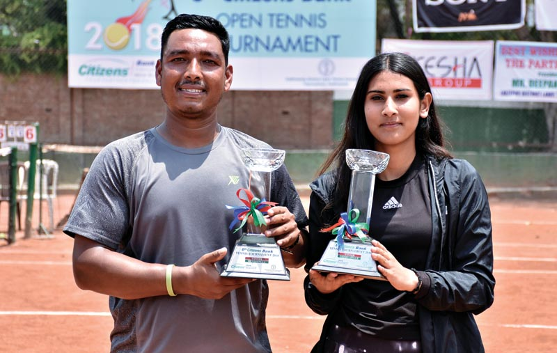 Jitendra Pariyar and Prerana Koirala hold the trophies after the sixth Citizens Bank Open Tennis Tournament in Kathmandu on Saturday, May 5, 2018. Photo: THT