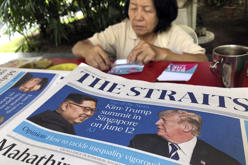 A news vendor counts her money near a stack of newspapers with a photo of US President Donald Trump, right, and North Korea's leader Kim Jong Un on its front page, in Singapore, on May 11, 2018. Photo: Associated Press/ File