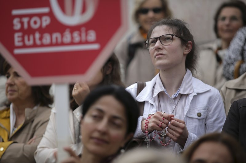 File - In this photo, people stand on the steps of the Portuguese parliament in Lisbon during a protest against euthanasia on May 24, 2018. Photo: AP