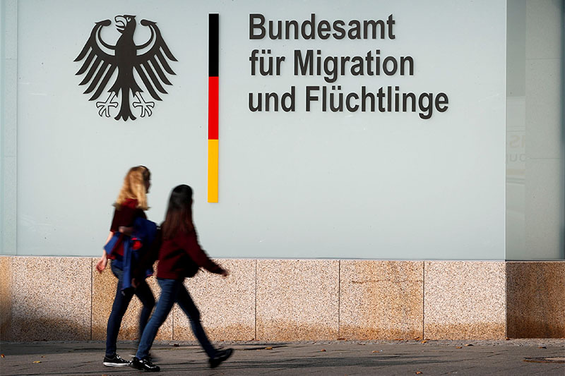FILE PHOTO: People walk in front of an office building of the Federal Office for Migration and Refugees (BAMF) in Berlin, Germany, October 15, 2017.  Photo: Reuters
