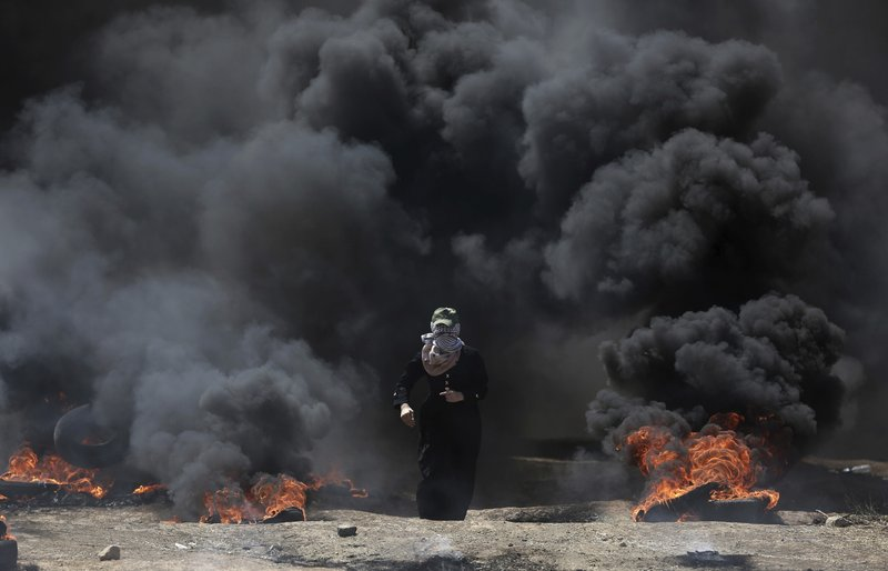 A Palestinian woman walks through black smoke from burning tires during a protest on the Gaza Stripu2019s border with Israel, on Monday, May 14, 2018. Photo: APn