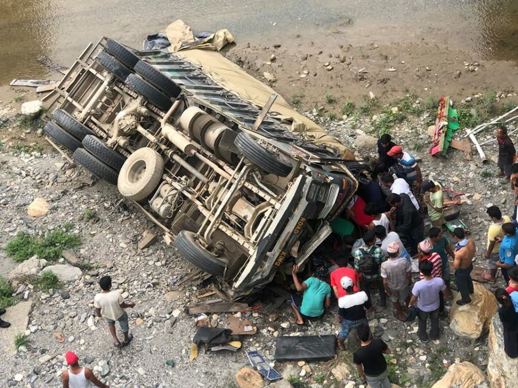 Locals and police personnel are seen inspecting the crushed hauler which plunged into Hugdi river after losing balance due to over speeding along Prithvi Highway, on May 23, 2018. Photo: Keshav Adhikari