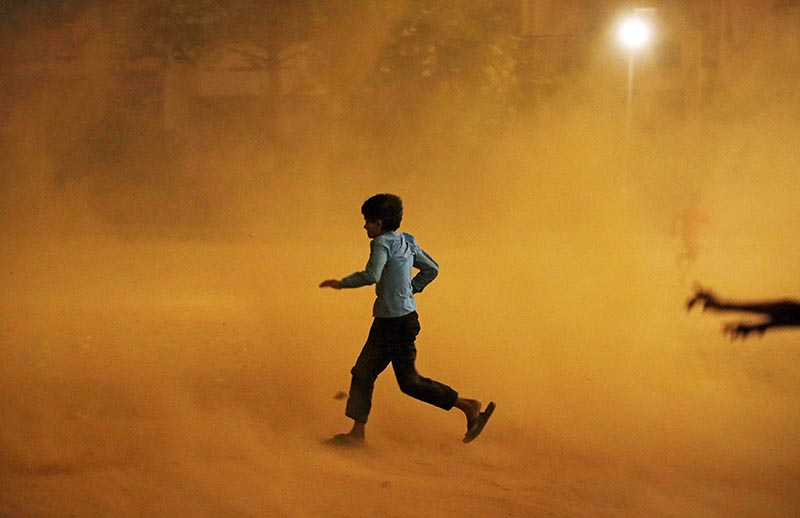 A boy runs for cover during a dust storm in New Delhi, India, on May 13, 2018. Photo: Reuters