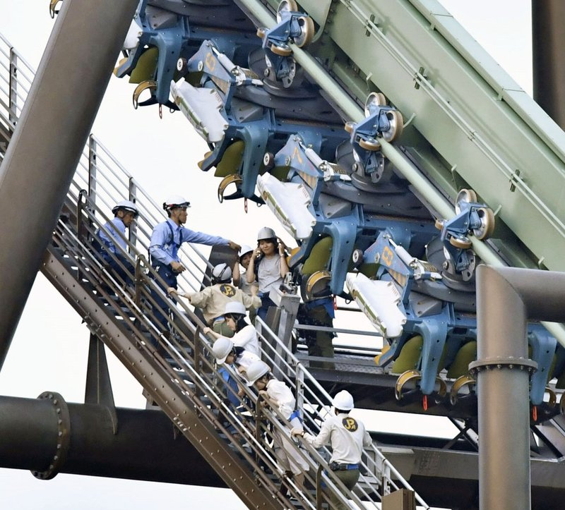 In this photo, passengers are rescued from the stopped Flying Dinosaur roller coaster at Universal Studios Japan amusement park in Osaka, western Japan on  Tuesday, May 1, 2018. Photo: AP