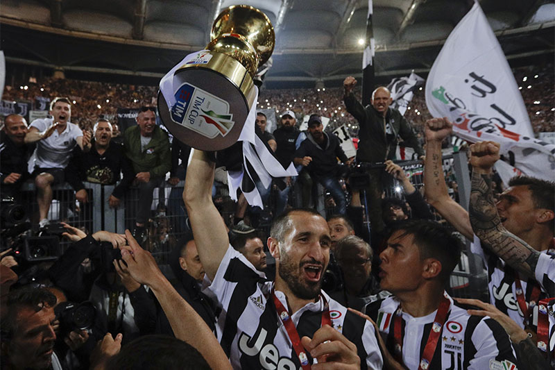 Juventus' Giorgio Chiellini holds up the trophy as he celebrates with teammates after beating AC Milan 4-0 in the Italian Cup final match, at the Rome Olympic stadium, on Wednesday, May 9, 2018. Photo: Associated Press