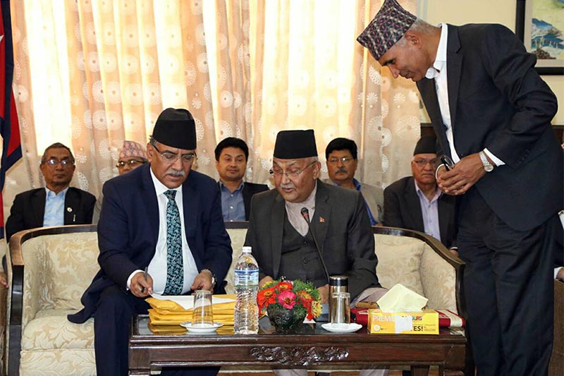Prime Minister KP Sharma Oli and Pushpa Kamal Dahal, who will co-chair the unified Nepal Communist Party, signing documents to  effect the merger of CPN-UML and CPN-Maoist Centre at the City Hall in Kathmandu, on Thursday, May 17, 2018. Photo: RSS