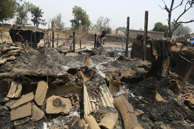 An Indian man inspects the damage after his home was gutted by firing allegedly, from the Pakistan side of the border in Jora farm village, in Ranbir Singh Pura district of Jammu and Kashmir, India, on Tuesday, May 22, 2018.