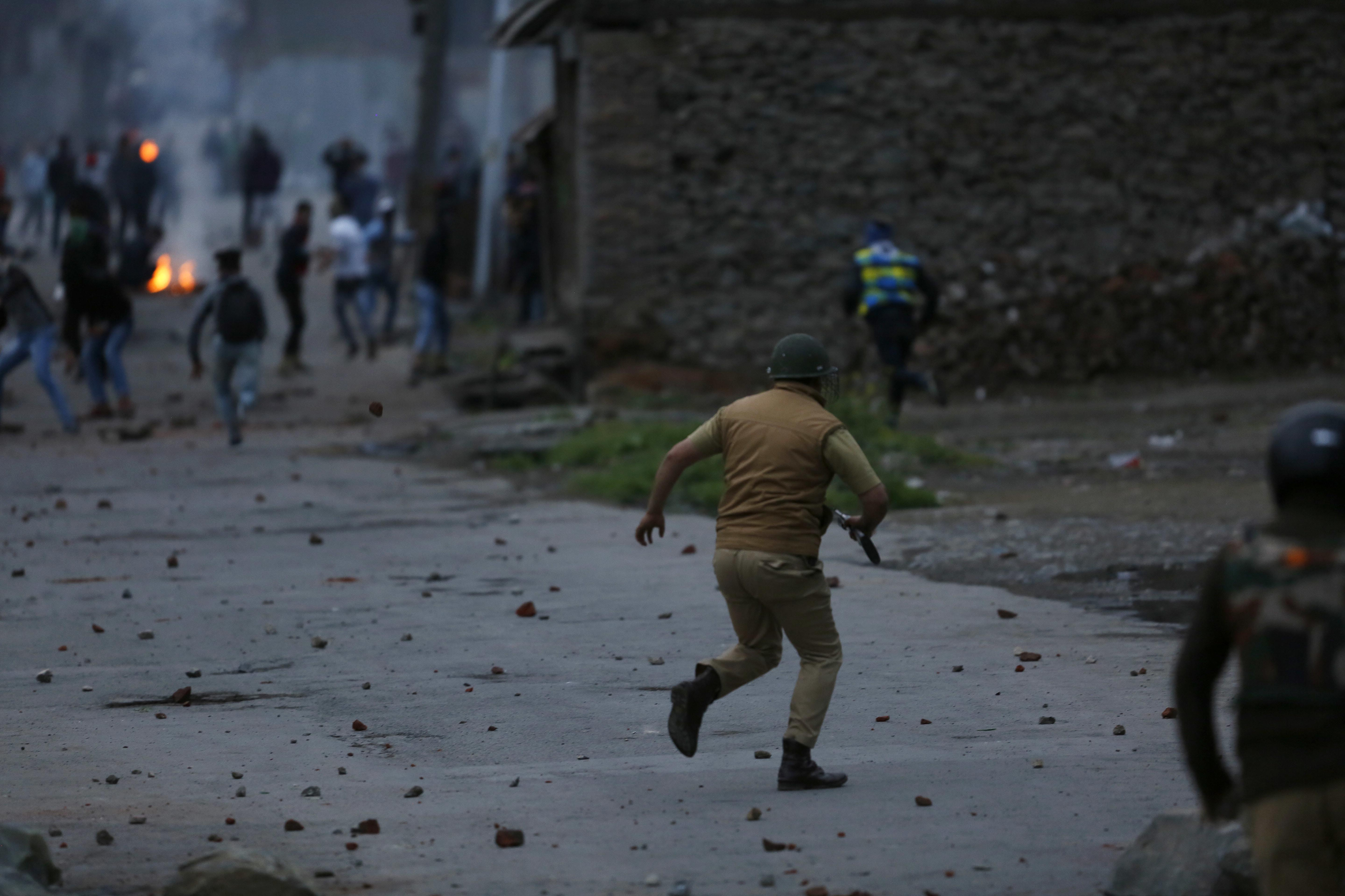 An Indian police officer chases stone throwing Kashmiri protesters in Srinagar, Indian controlled Kashmir, on Monday, May 7, 2018.