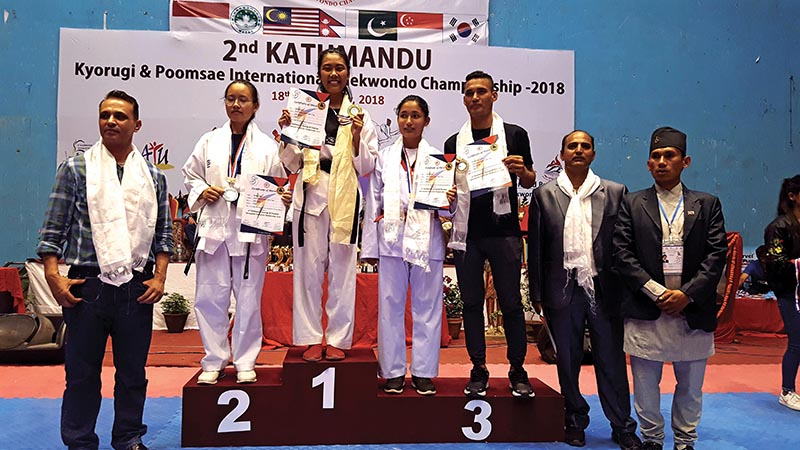 Rubina Ghale of Newgen holds the gold medal as other players and officials pose for a group photo after the second Kathmandu International Taekwondo Championship in Kathmandu on Sunday. Photo: THT