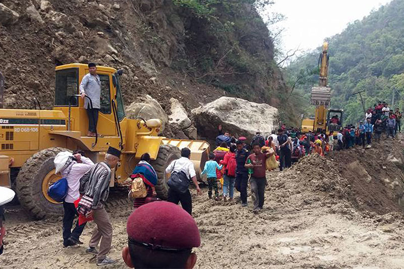 Stranded passengers trying to walk though landslide debris as heavy equipments deployed at Headbox along Butwal--Palpa road section in Siddhartha Highway, on Sunday, May 14, 2018. Photo: RSS