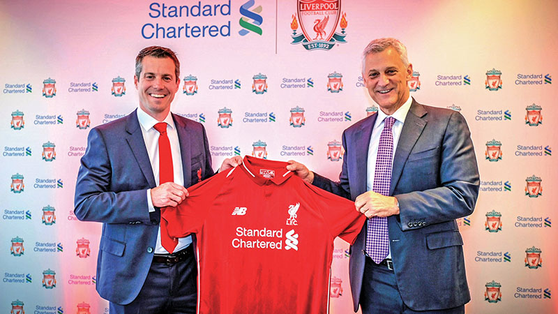 Liverpool MD Billy Hogan (left) and Standard Chartered Bank CEO Bill Winters hold the club jersey.