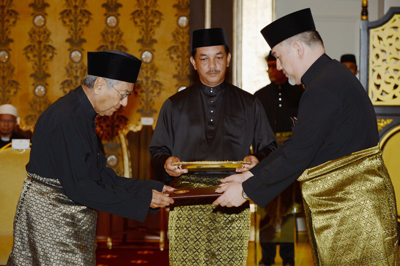 Mahathir Mohamad, left, receives official documentation from Malaysia's King Muhammad V, right, as he was sworn in as Malaysia's new prime minister at the National Palace in Kuala Lumpur, Malaysia, on Thursday, May 10, 2018. Photo: Associated Press