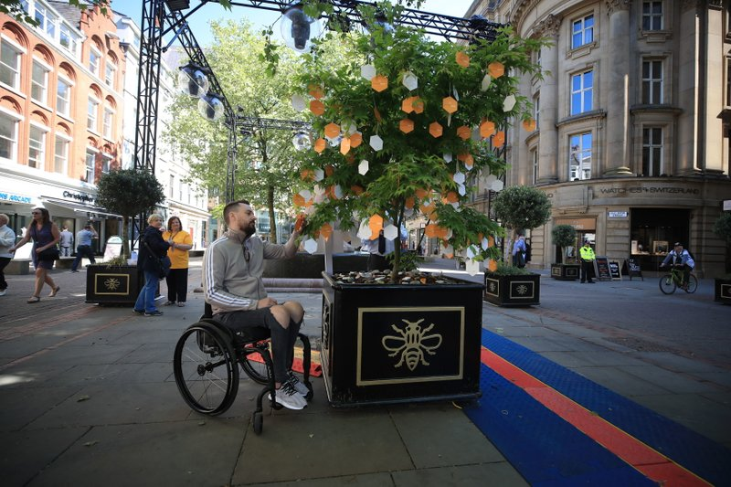 Martin Hibbertt, who suffered life-changing injuries in the Manchester terror attack, reads messages left on a u2018Tree of Hopeu2019 in St Annu2019s Square, Manchester, England ahead of the Manchester Arena National Service of Commemoration at Manchester Cathedral to mark one year since the attack, on Tuesday May 22, 2018. Photo: APn