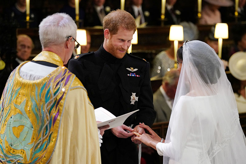 Prince Harry places the wedding ring on the finger of Meghan Markle in St George's Chapel at Windsor Castle during their wedding service, conducted by the Archbishop of Canterbury Justin Welby, in Windsor, Britain, on Saturday, May 19, 2018. Photo: Reuters