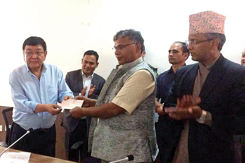 Minister of Industry, Commerce and Supplies Matrika Prasad Yadav handing over a cheque to Executive Director of Tilganga Institute of Ophthalmology Dr Sanduk Ruit, on Tuesday, May 8, 2018. Photo: THT