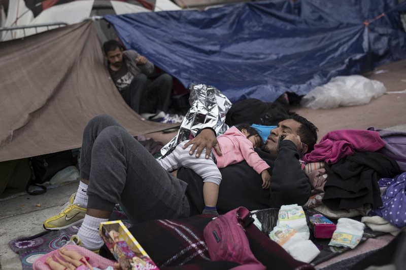A migrant father and child, who traveled with the annual caravan of Central American migrants, rest where they set up camp to wait for access to request asylum in the US, outside the El Chaparral port of entry building at the US-Mexico border in Tijuana, Mexico, on Monday, April 30, 2018. Photo: AP